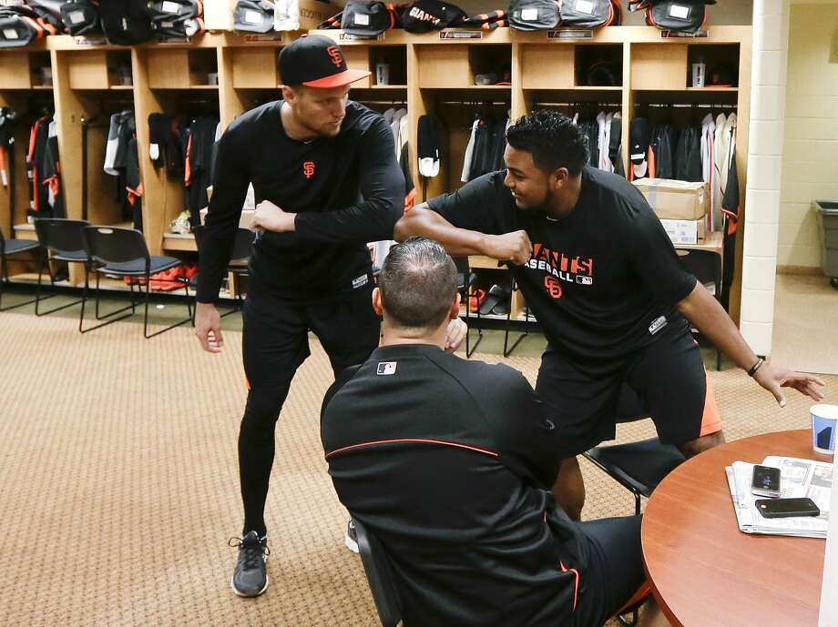 Hunter Pence (left) greets Jean Machi (right) in front of Guillermo Quiroz in the clubhouse in Scottsdale. Photo: Gregory Bull, Associated Press