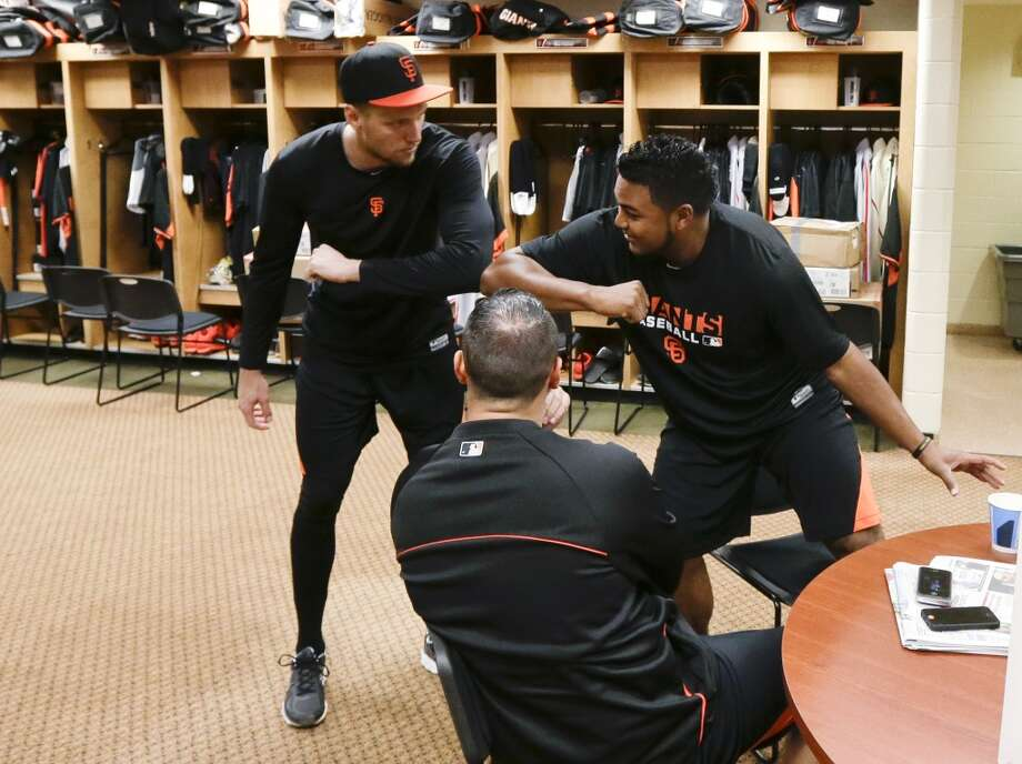San Francisco Giants outfielder Hunter Pence, left, greets pitcher Jean Machi, right, as catcher Guillermo Quiroz watches in the locker room at baseball spring training, Friday, Feb. 14, 2014, in Scottsdale, Ariz. Photo: Gregory Bull, Associated Press
