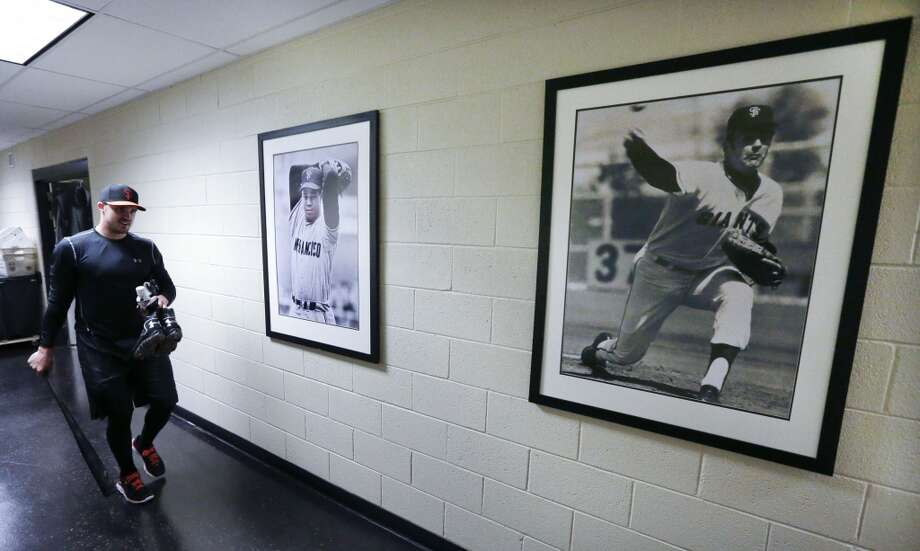 San Francisco Giants third baseman Adam Duva walks past pictures of former Giants pitchers Juan Marichal, lert, and Gaylord Perry during baseball spring training Friday, Feb. 14, 2014, in Scottsdale, Ariz. Photo: Gregory Bull, Associated Press