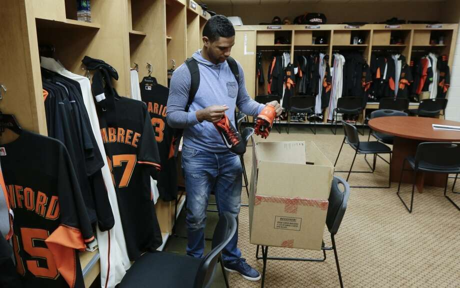 San Francisco Giants pitcher Sandy Rosario unpacks a pair of shoes as he arrives for spring training baseball practice on Friday, Feb. 14, 2014, in Scottsdale, Ariz. Giants pitchers and catchers arrived on Friday for physicals before beginning training on Saturday. Photo: Gregory Bull, Associated Press