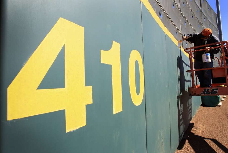 Lou Aviles freshens up the yellow paint on the home run marker in the outfield as preparations were underway in anticipation of the start of the Astros spring training at the Osceola County Stadium in Kissimmee, Fla. Photo: Karen Warren, Houston Chronicle