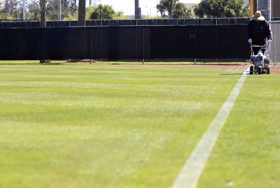 Groundskeeper Hiram Rodriguez paints foul lines on the practice fields as preparations were underway in anticipation of the start of the Astros spring training at the Osceola County Stadium in Kissimmee, Fla. Photo: Karen Warren, Houston Chronicle