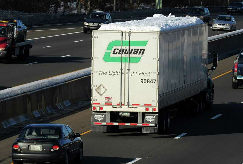 Snow covers the roof of a tractor-trailer as it travels on I-95 northbound on Friday, Feb. 14, 2014.