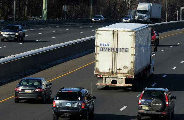 "Snow covers the roof of a tractor-trailer as it travels on I-95 northbound on Friday, Feb. 14, 2014. A new state ""ice-missile""  law requires motorists to scrape off snow and ice from hoods, trunks and roofs. Photo: Christian Abraham / Connecticut Post"
