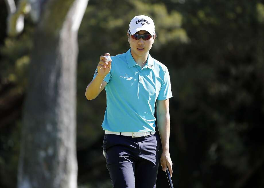 Sang-Moon Bae acknowledges the crowd after saving par on No. 12 at the Northern Trust Open. Photo: Reed Saxon, Associated Press