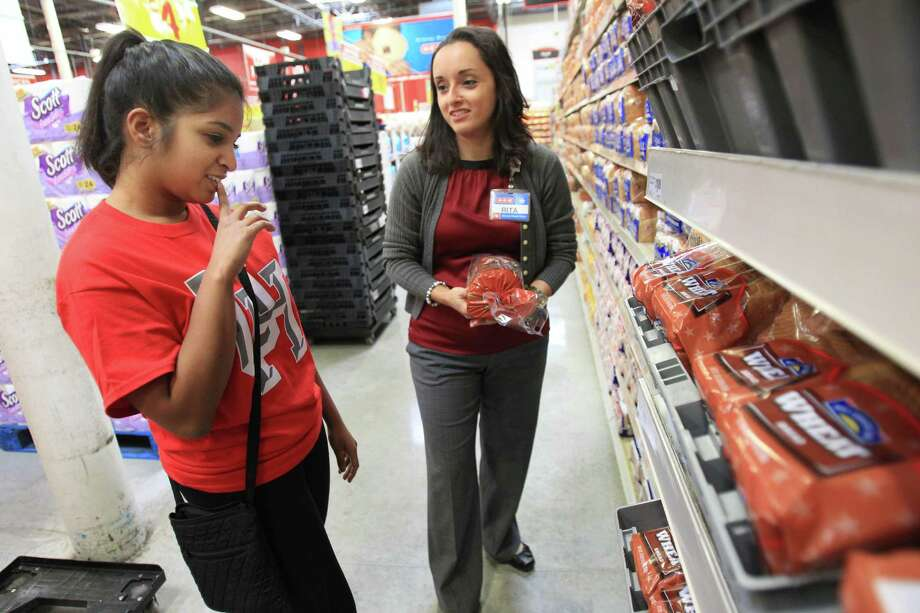 Misha Chishty, University of Houston student, shoping with Rita Zapien, HEB Houston Regional Dietitian, decides on what type of bread she can afford with the most nutrition. Photo: Mayra Beltran, Houston Chronicle / © 2014 Houston Chronicle