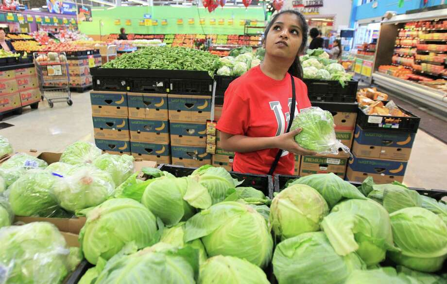 Misha Chishty decides between purchasing iceberg lettuce or cabbage, which is a cheaper option. Photo: Mayra Beltran, Houston Chronicle / © 2014 Houston Chronicle