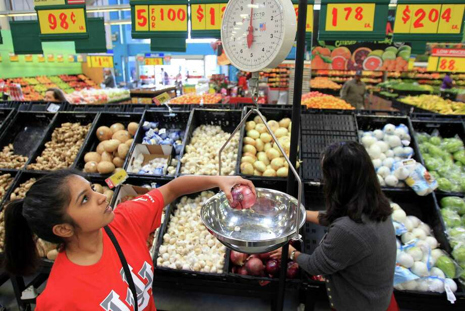 Misha Chishty weights a red onion while shopping with Rita Zapien, HEB Houston Regional Dietitian. Photo: Mayra Beltran, Houston Chronicle / © 2014 Houston Chronicle