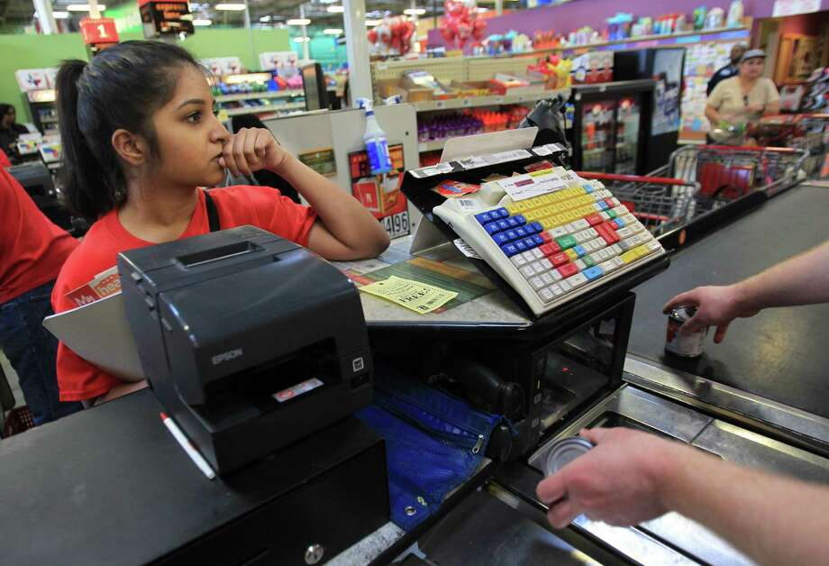 Misha Chishty stares at the total while an HEB clerk rings up food items as she concludes her shopping. Photo: Mayra Beltran, Houston Chronicle / © 2014 Houston Chronicle