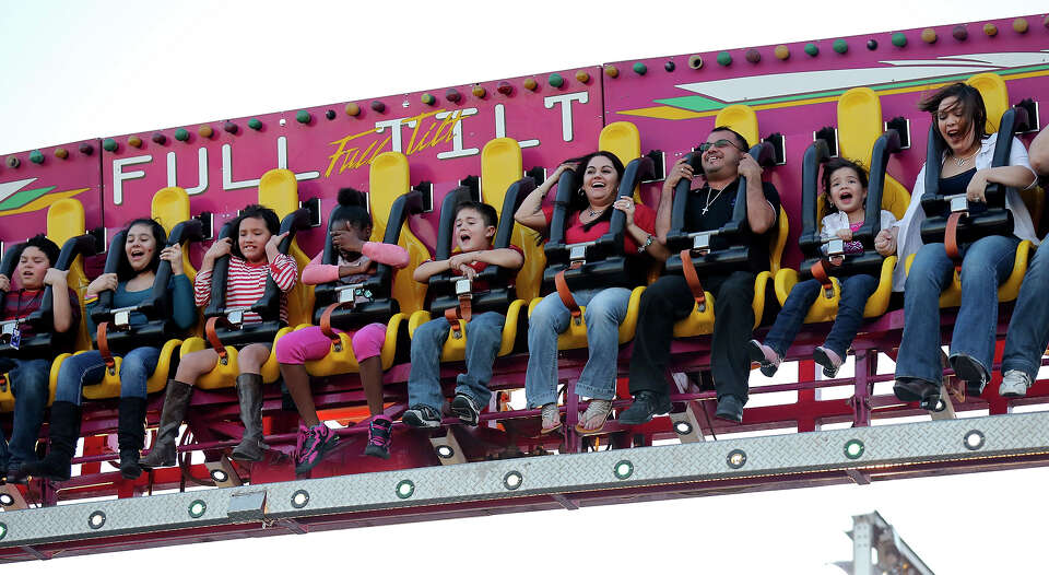 Enjoying the mild weather people ride the Full Tilt at the Wade Shows Carnival during the San Antoni