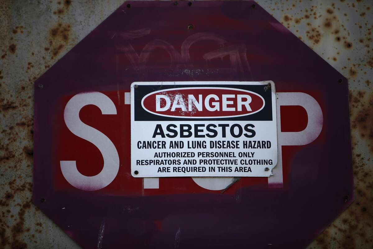 A sign warning of asbestos in a building is placed over a stop sign on the door on a building along 9th Street on Wednesday, September 11, 2013 on Treasure Island in San Francisco, Calif.