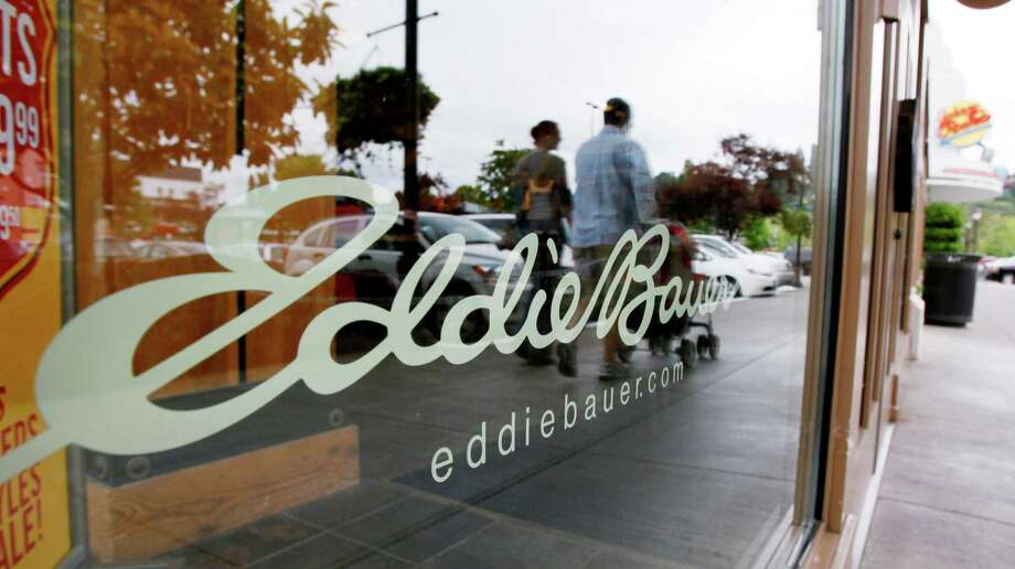 FILE - In this Wednesday, June 17, 2009, file photo, shoppers are reflected in the window as they walk past an Eddie Bauer store, in Seattle. Jos. A. Bank Clothiers Inc. said Friday, Feb. 14. 2014, it is buying the parent company of Eddie Bauer in a cash-and-stock deal valued at $825 million that will help strengthen its men's wear business and diversify its offerings. (AP Photo/Elaine Thompson, File) ORG XMIT: NYBZ151 Photo: Elaine Thompson / AP