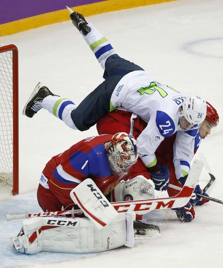 Slovenia forward Rok Ticar falls over Russia goaltender Semyon Varlamov and defenseman Alexei Yemelin in the third period of a men's ice hockey game at the 2014 Winter Olympics, Thursday, Feb. 13, 2014, in Sochi, Russia. (AP Photo/Mark Humphrey) Photo: Mark Humphrey, Associated Press