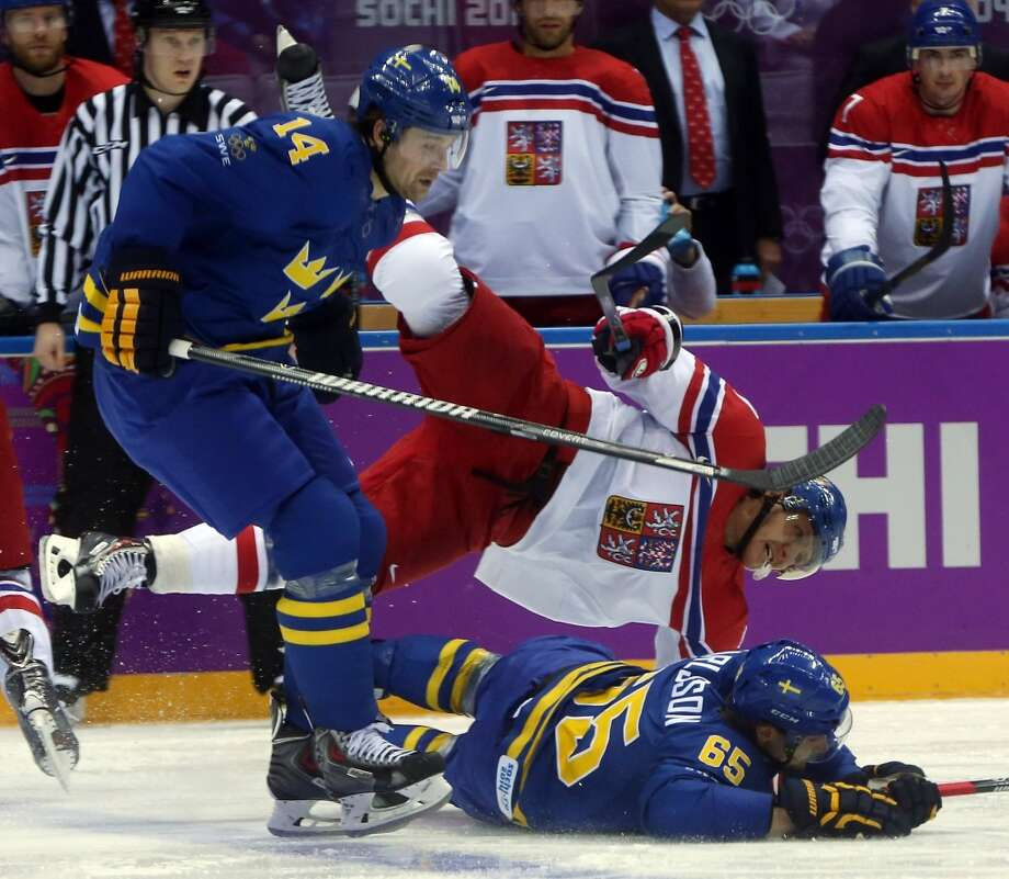Czech Republic's Martin Erat (91) falls over Sweden's Erik Karlsson (65) in the second period of a men's hockey game at the Winter Olympics in Sochi, Russia, Wednesday, Feb. 12, 2014. (Brian Cassella/Chicago Tribune/MCT) Photo: McClatchy-Tribune News Service
