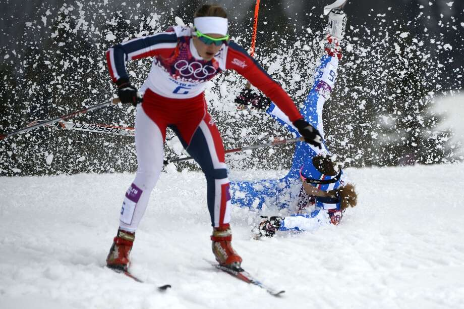 TOPSHOTS Italy's Greta Laurent falls as Norway's Ingvild Flugstad Oestberg skis past as they compete in the Women's Cross-Country Skiing Individual Sprint Free Quarterfinals at the Laura Cross-Country Ski and Biathlon Center during the Sochi Winter Olympics on February 11, 2014 in Rosa Khutor near Sochi. AFP PHOTO / PIERRE-PHILIPPE MARCOUPIERRE-PHILIPPE MARCOU/AFP/Getty Images Photo: AFP/Getty Images
