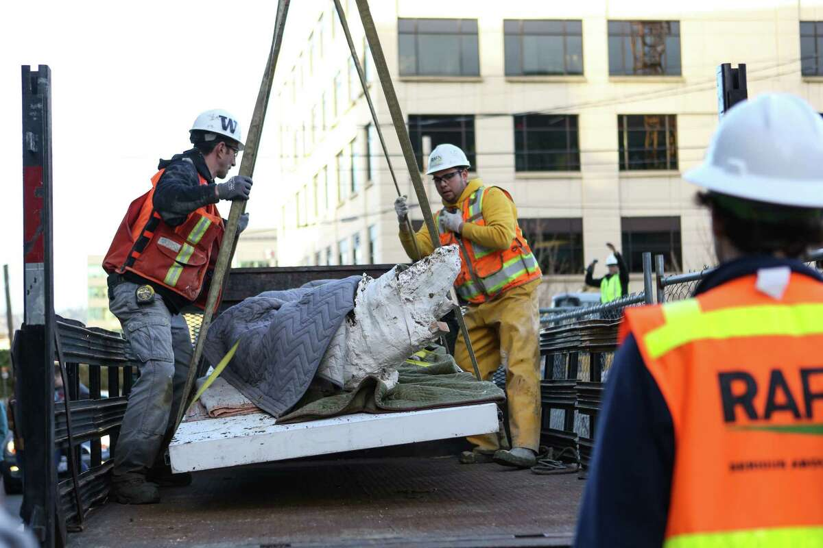 Workers lower a fossilized and plaster-wrapped mammoth tusk with a crane as it is removed from a construction pit in Seattle's South Lake Union neighborhood on Friday, Feb. 14, 2014. The ancient remain was discovered by a crew working on plumbing 60 feet down in the pit. The tusk is 8.5 feet long and is the largest and most complete mammoth tusk found to date in Seattle. It will be cared for by the Burke Museum until ownership of the tusk can be worked out with the apartment developer.