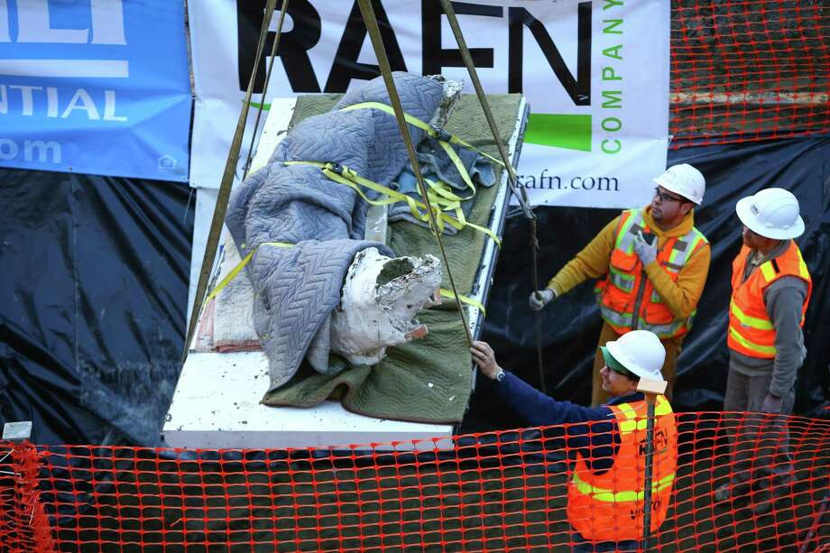 Workers use a crane to remove a fossilized mammoth tusk from a construction pit. Photo: JOSHUA TRUJILLO, SEATTLEPI.COM / SEATTLEPI.COM