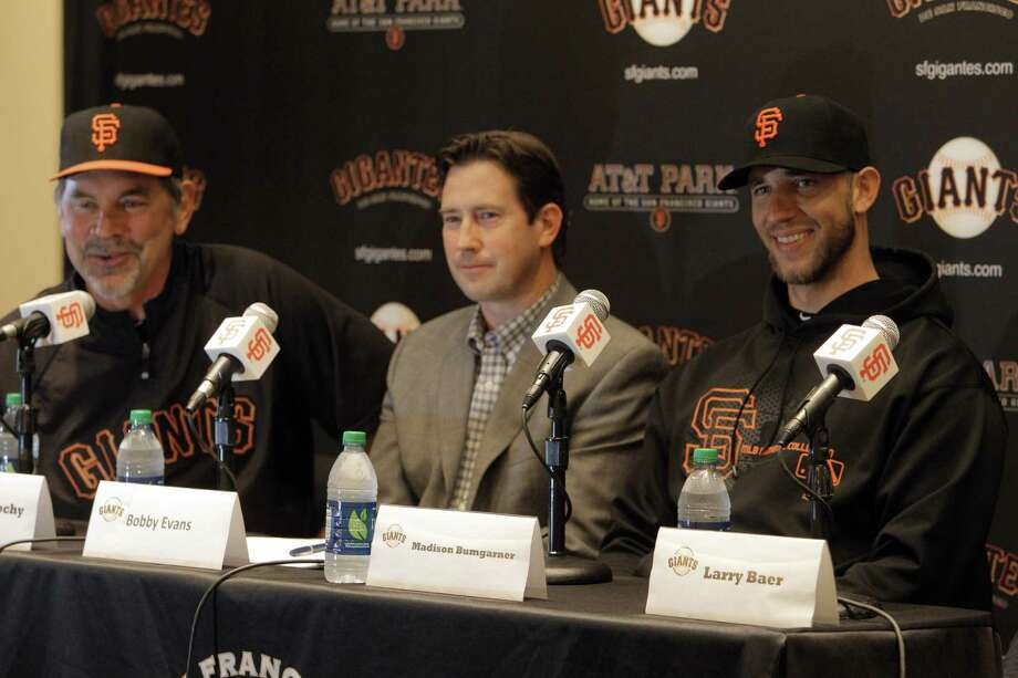 Madison Bumgarner, right, and Bobby Evans, center, listen as Giants Manager Bruce Bochy answers questions from the press after the San Francisco Giants announced a 5-year contract extension for the pitcher at AT&T Park in San Francisco, Calif., on Monday, April 16, 2012. Photo: Carlos Avila Gonzalez / The Chronicle / ONLINE_YES