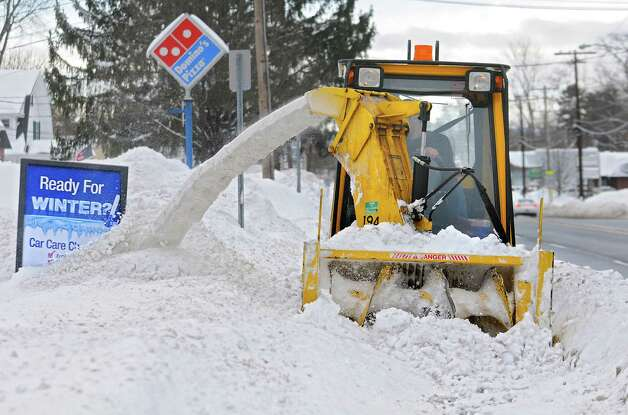 A sidewalk snow removal vehicle dumps snow on a sign along Delaware Ave. Friday, Feb. 14, 2014, in Delmar, N.Y.  (Lori Van Buren / Times Union) Photo: Lori Van Buren / 0025756A