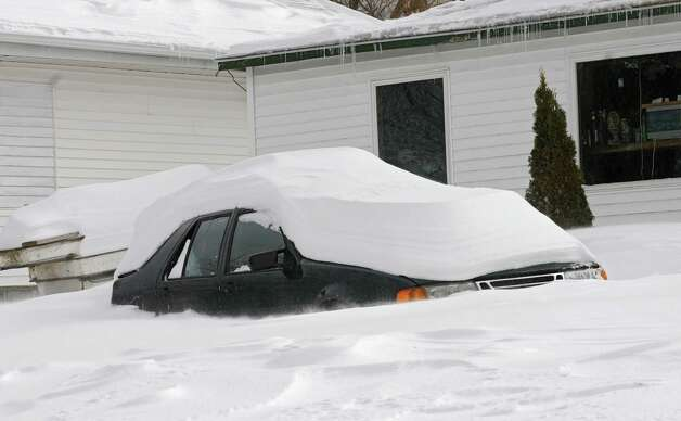 A car is almost completely covered with snow in front of a home on Warners Lake Friday, Feb. 14, 2014, in East Berne, N.Y.  (Lori Van Buren / Times Union) Photo: Lori Van Buren / 0025756A