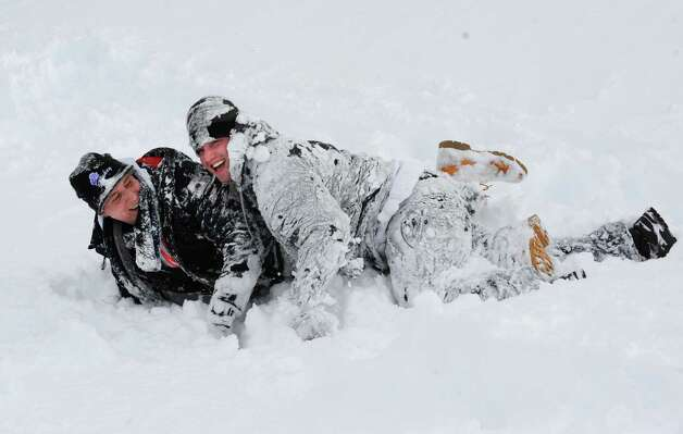 Ryan Jones of Woodbury, NY, left, and his friend Nikolas Martino of Albany get covered with snow as they roll down a hill at Lincoln Park Friday, Feb. 14, 2014, in Albany, N.Y.  (Lori Van Buren / Times Union) Photo: Lori Van Buren / 0025756A