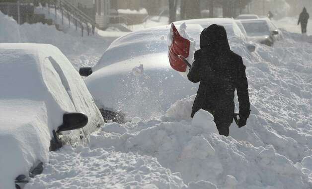 Ricardo Lopez clears snow from around his car after getting blocked in by snow plows Friday morning Feb. 14, 2014, on Washington Avenue in Albany, N.Y. (Skip Dickstein / Times Union) Photo: Skip Dickstein