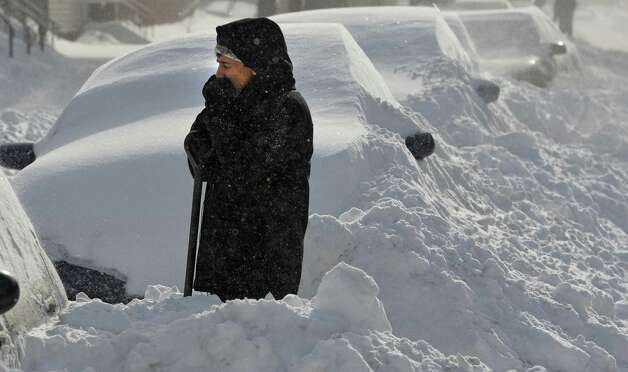 Ricardo Lopez takes a break to warms his hands while removing snow from his car Friday morning, Feb. 14, 2014, on Washington Avenue in Albany, N.Y. (Skip Dickstein / Times Union) Photo: Skip Dickstein