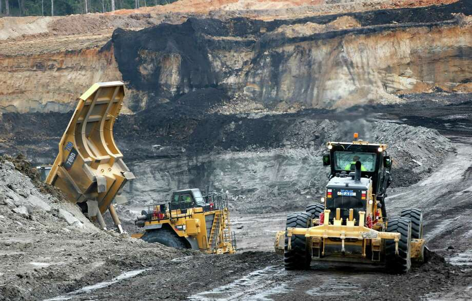 An earth mover and a dump truck move through a pit adjacent to a Mississippi Power plant near DeKalb, Miss. The plant removes carbon dioxide and keeps it out of the atmosphere. Photo: Rogelio V. Solis, STF / AP