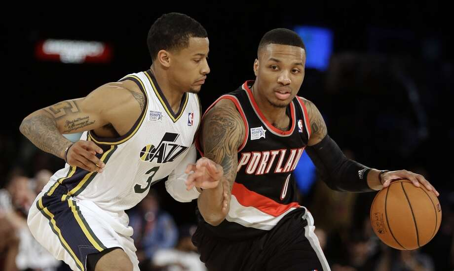 Team Hill's Damian Lillard of the Portland Trail Blazers, right, moves the ball against Team Webber's Trey Burke of the Utah Jazz during the Rising Star NBA All Star Challenge Basketball game, Friday, Feb. 14, 2014, in New Orleans. (AP Photo/Gerald Herbert) Photo: Gerald Herbert, Associated Press
