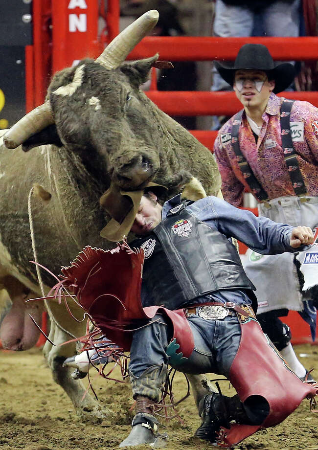 Corey Atwell, of Moravian Falls, NC, tries to get away from his bull in the bull riding event during the San Antonio Stock Show & Rodeo Friday Feb. 14, 2014 at the AT&T Center. Atwell scored a 77 on the ride. Photo: Edward A. Ornelas, San Antonio Express-News / © 2014 San Antonio Express-News