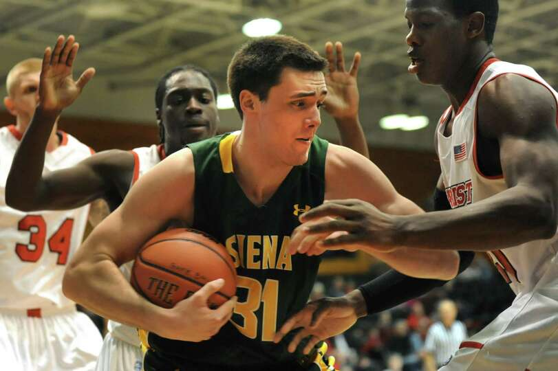 Siena's Brett Bisping, center, protects the ball during their basketball game against Marist on Frid