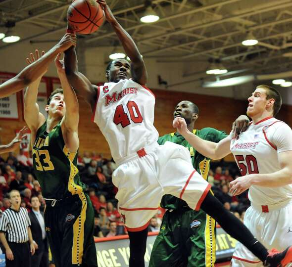Marist's Chavaughn Lewis, center, wins the rebound over Siena's Rob Poole, left, during their basket