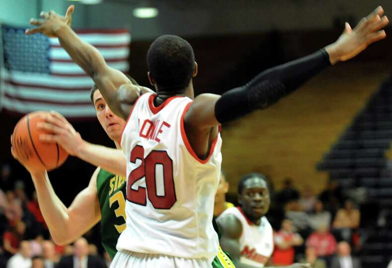 Siena's Brett Bisping, left, looks to pass as Marist's Jay Bowie defends during their basketball gam