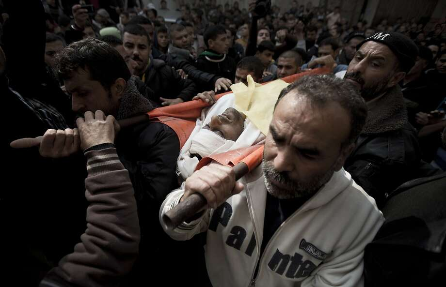TOPSHOTS Palestinian mourners carry the body of Ibrahim Suleiman Mansur, who was shot dead by Israeli troops near the border fence between Israel and the Gaza Strip, on February 14, 2014 during his funeral in Gaza City.   AFP PHOTO / MAHMUD HAMSMAHMUD HAMS/AFP/Getty Images Photo: Mahmud Hams, AFP/Getty Images