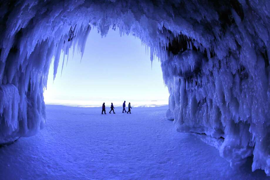 In this Feb. 2, 2014 photo people visit the caves at  Apostle Islands National Lakeshore in northern Wisconsin, transformed into a dazzling display of ice sculptures by the arctic siege gripping the Upper Midwest. The caves are usually are accessible only by water, but Lake Superior's rock-solid ice cover is letting people walk to them for the first time since 2009.  (AP Photo/The Minneapolis Star Tribune, Brian Peterson) MANDATORY CREDIT; ST. PAUL PIONEER PRESS OUT; MAGS OUT; TWIN CITIES TV OUT ORG XMIT: MNMIT201 Photo: Brian Peterson, AP / Minneapolis Star Tribune