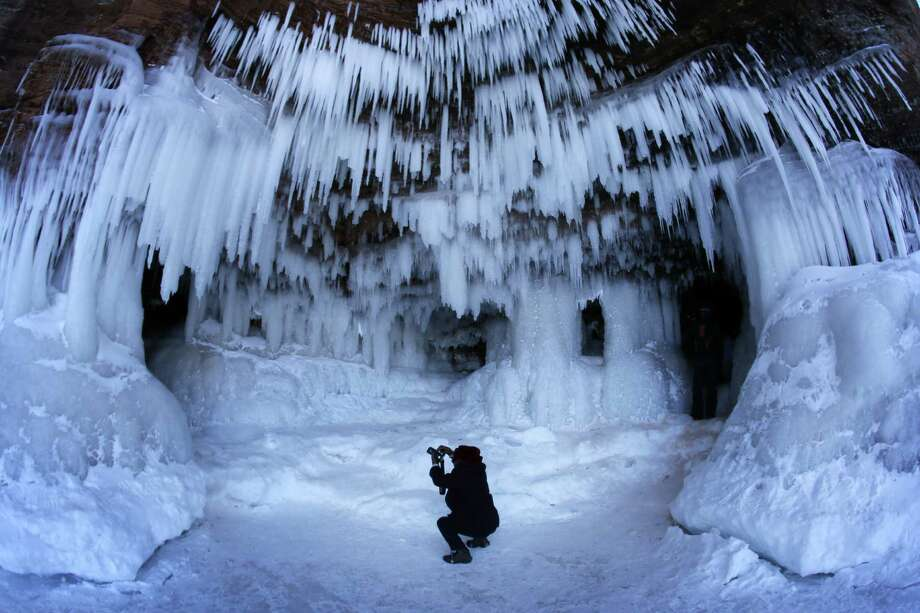 In this Feb. 2, 2014 photo people visit the caves at  Apostle Islands National Lakeshore in northern Wisconsin, transformed into a dazzling display of ice sculptures by the arctic siege gripping the Upper Midwest. The caves are usually are accessible only by water, but Lake Superior's rock-solid ice cover is letting people walk to them for the first time since 2009. (AP Photo/Minneapolis Star Tribune, Brian Peterson) ORG XMIT: MNMIT505 Photo: Brian Peterson, AP / Minneapolis Star Tribune