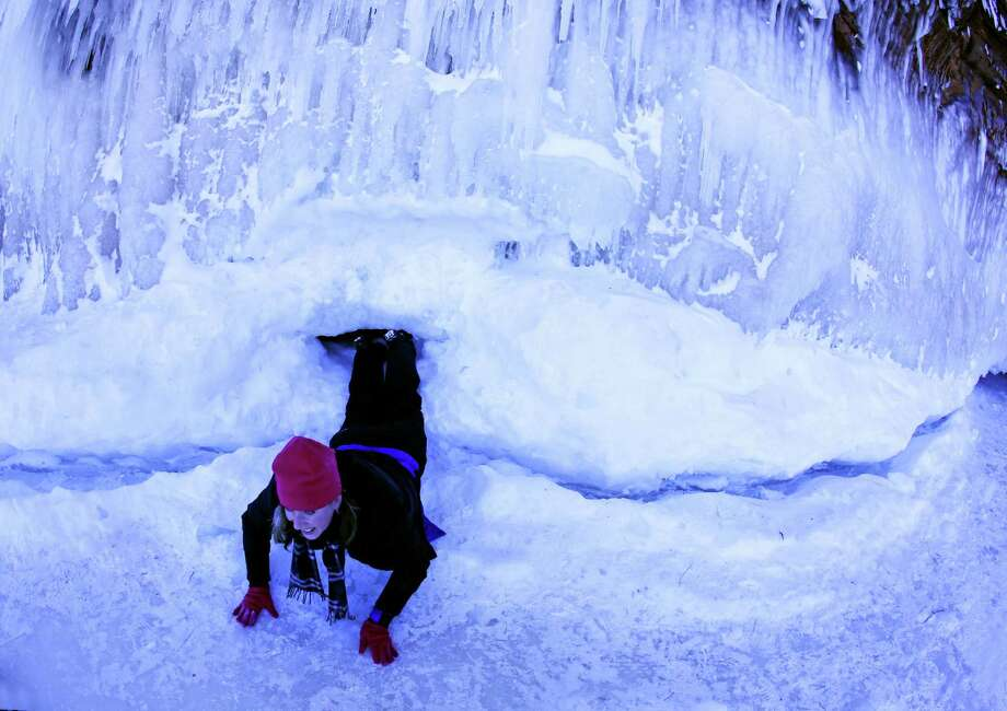 In this Feb. 2, 2014 photo people visit the caves at  Apostle Islands National Lakeshore in northern Wisconsin, transformed into a dazzling display of ice sculptures by the arctic siege gripping the Upper Midwest. The caves are usually are accessible only by water, but Lake Superior's rock-solid ice cover is letting people walk to them for the first time since 2009. (AP Photo/Minneapolis Star Tribune, Brian Peterson) MANDATORY CREDIT; ST. PAUL PIONEER PRESS OUT; MAGS OUT; TWIN CITIES TV OUT ORG XMIT: MNMIT509 Photo: Brian Peterson, AP / Minneapolis Star Tribune