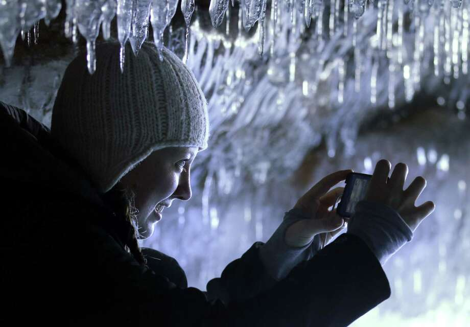 In this Feb. 2, 2014 photo people visit the caves at  Apostle Islands National Lakeshore in northern Wisconsin, transformed into a dazzling display of ice sculptures by the arctic siege gripping the Upper Midwest. The caves are usually are accessible only by water, but Lake Superior's rock-solid ice cover is letting people walk to them for the first time since 2009. (AP Photo/Minneapolis Star Tribune, Brian Peterson) MANDATORY CREDIT; ST. PAUL PIONEER PRESS OUT; MAGS OUT; TWIN CITIES TV OUT ORG XMIT: MNMIT504 Photo: Brian Peterson, AP / Minneapolis Star Tribune