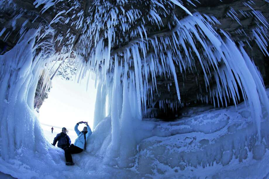 In this Feb. 2, 2014 photo, people take pictures inside a cave at Apostle Islands National Lakeshore in northern Wisconsin, which has been transformed into a dazzling display of ice sculptures by the arctic siege gripping the Upper Midwest. The caves are usually are accessible only by water, but Lake Superior's rock-solid ice cover is letting people walk to them for the first time since 2009. (AP Photo/The Star Tribune, Brian Peterson)  MANDATORY CREDIT; ST. PAUL PIONEER PRESS OUT; MAGS OUT; TWIN CITIES TV OUT ORG XMIT: MNMIT512 Photo: Brian Peterson, AP / Minneapolis Star Tribune