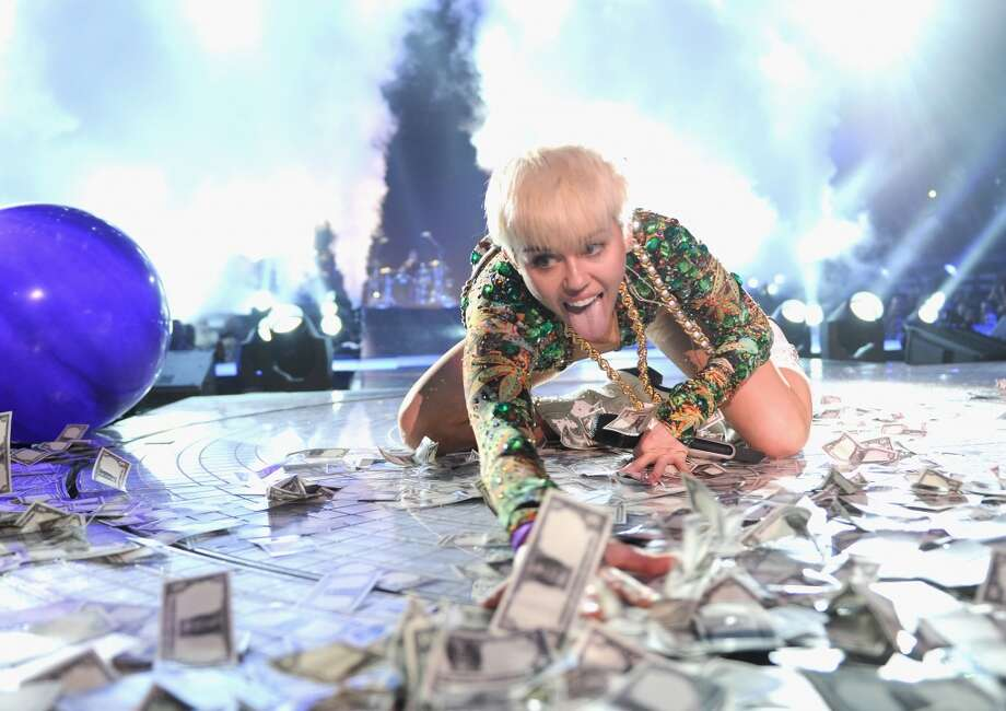 "Miley Cyrus rolls in money during her ""Bangerz"" tour at Rogers Arena on February 14, 2014 in Vancouver, Canada. Photo: Kevin Mazur, WireImage"