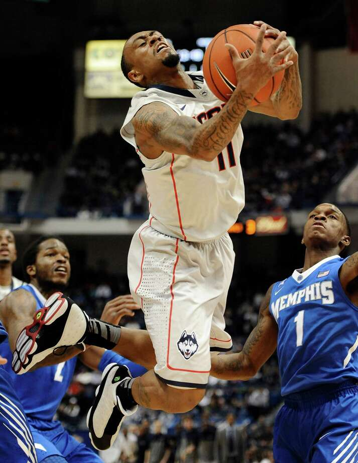 Connecticut's Ryan Boatright is fouled and flies out-of-bounds as Memphis' Shaq Goodwin, left, and Joe Jackson, right, defend during the first half of an NCAA college basketball game. Photo: Jessica Hill, AP / Associated Press