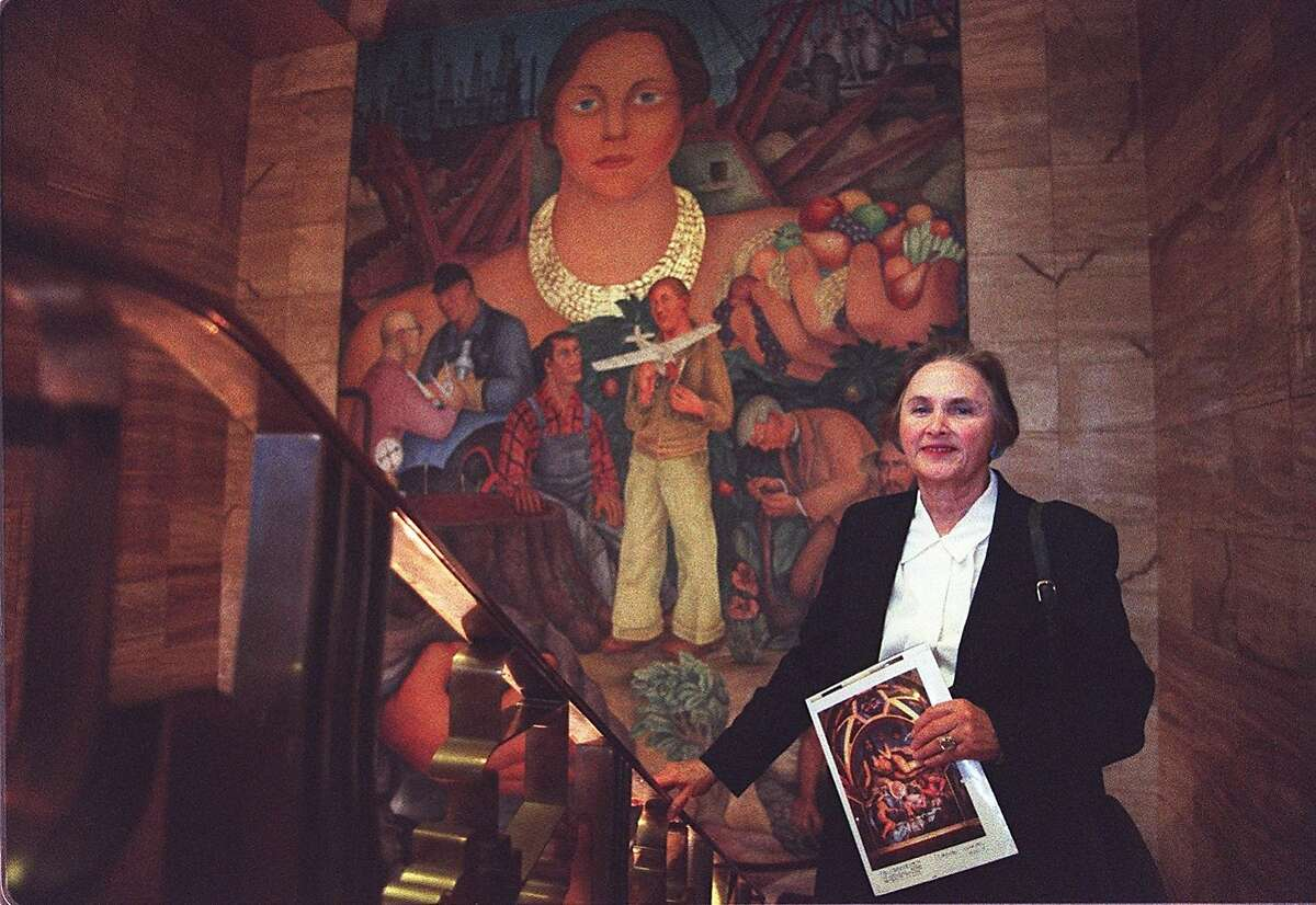 DIFFERENCE/C/08FEB96/MN/DF - Masha Zakheim stands next to a Diego Riviera mural in the City Club at SF Stock Exchange. She gives free art/architecture tours there. CHRONICLE PHOTO BY DEANNE FITZMAURICE