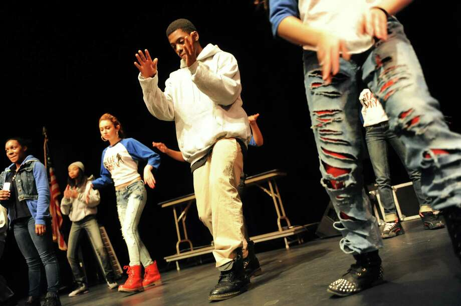 Emagji Utsey, 19, center, captain of Team Onyx, an Albany-based hip hop troupe, runs through a routine before performing for the Black and Puerto Rican Caucus Youth Summit on Saturday, Feb. 15, 2014, at The Egg in Albany, N.Y. The dancers practice Monday through Friday nights at the Arbor Hill Community Center. (Cindy Schultz / Times Union) Photo: Cindy Schultz / 00025768A