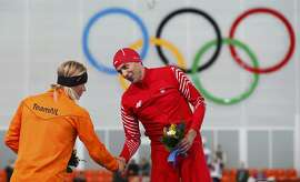 Winner of the men's 1,500 metres speed skating competition Zbigniew Brodka of Poland (R) shakes hands with second-placed Koen Verweij of the Netherlands at the flower ceremony for the event at the 2014 Sochi Winter Olympics, February 15, 2014.    REUTERS/Marko Djurica (RUSSIA  - Tags: OLYMPICS SPORT SPEED SKATING)