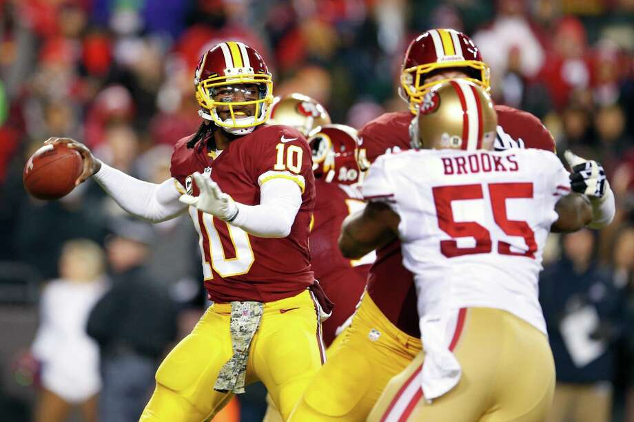 Washington Redskins quarterback Robert Griffin III prepares to pass the ball as San Francisco 49ers outside linebacker Ahmad Brooks closes in during the first half of an NFL football game in Landover, Md., Monday, Nov. 25, 2013. (AP Photo/Evan Vucci) Photo: Evan Vucci, Associated Press / AP