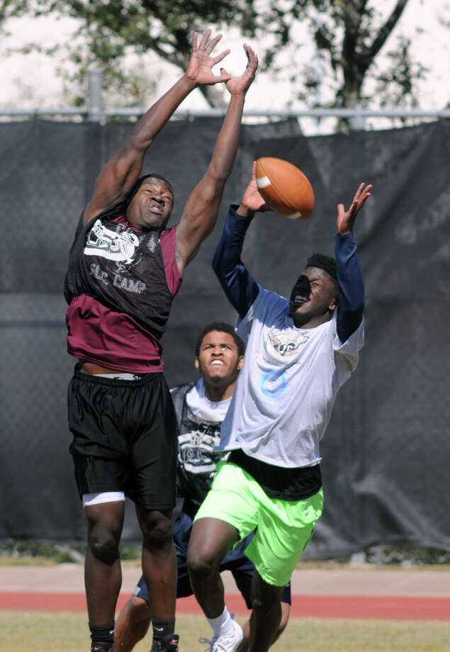 Jarvis Hogan, Jr., right, a tight end/wide receiver from Klein Collins High School, hauls in a pass in front of Cy-Fair High School defensive lineman/linebacker Michael Omirin, left, and Lamar High School wide receiver Daijon Druhet during the 7 on 7 competition at the 6th Annual Greater Houston Senior Football Showcase at the Methodist Training center at Reliant Stadium on Saturday. Photo: Jerry Baker, For The Chronicle