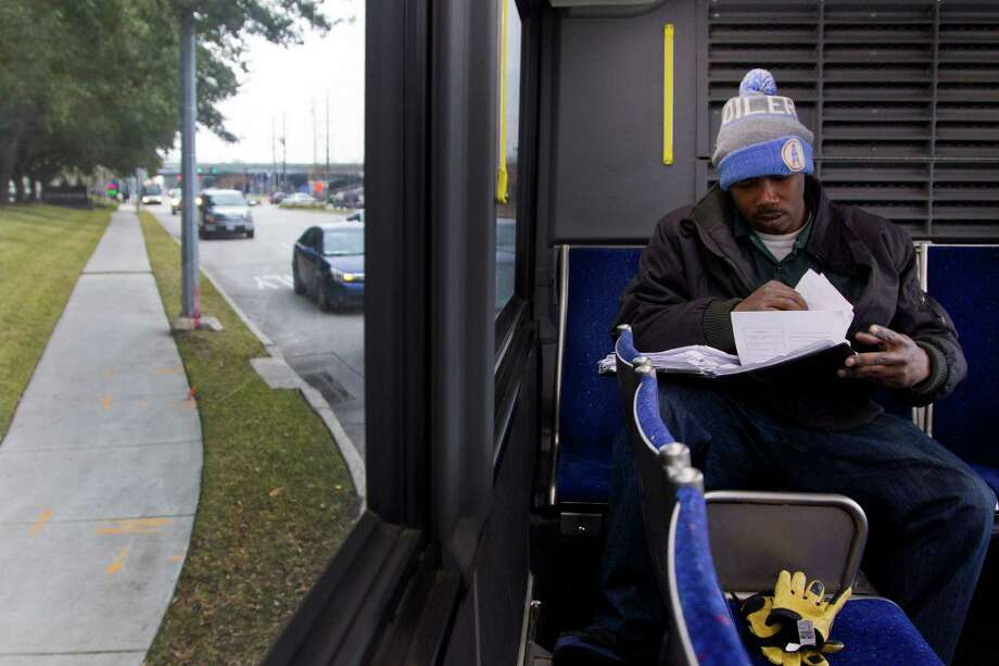 Jerome Edmond, a 34-year-old retired Army veteran, gets his homework out as he rides the 86 bus from Greenspoint, Thursday, Feb. 6, 2014.  Edmond has to take three buses from his home to a stop about 20 miles away near Ella Boulevard and West Airtex, and then walks nearly three miles to get to school at the MIAT Institute of Technology. The one-way commute takes roughly two and a half hours and Edmond does it twice a day, five days a week. Photo: Karen Warren, Houston Chronicle / © 2013 Houston Chronicle