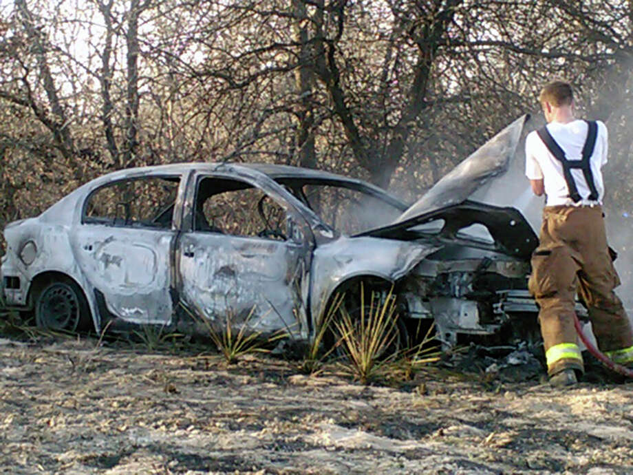 Harmony Volunteer Fire Department firefighter Preston Welch inspects the shell of a car at the scene of a brush fire on Saturday afternoon.  Crews from four area fire departments battled the brush fire on the far Southeast Side after the wrecked car burst into flames. It was unclear what happened to the driver or how many passengers were involved, if any. At least one woman suffered from smoke inhalation, but no other injuries were reported. Photo: Mark Wilson
