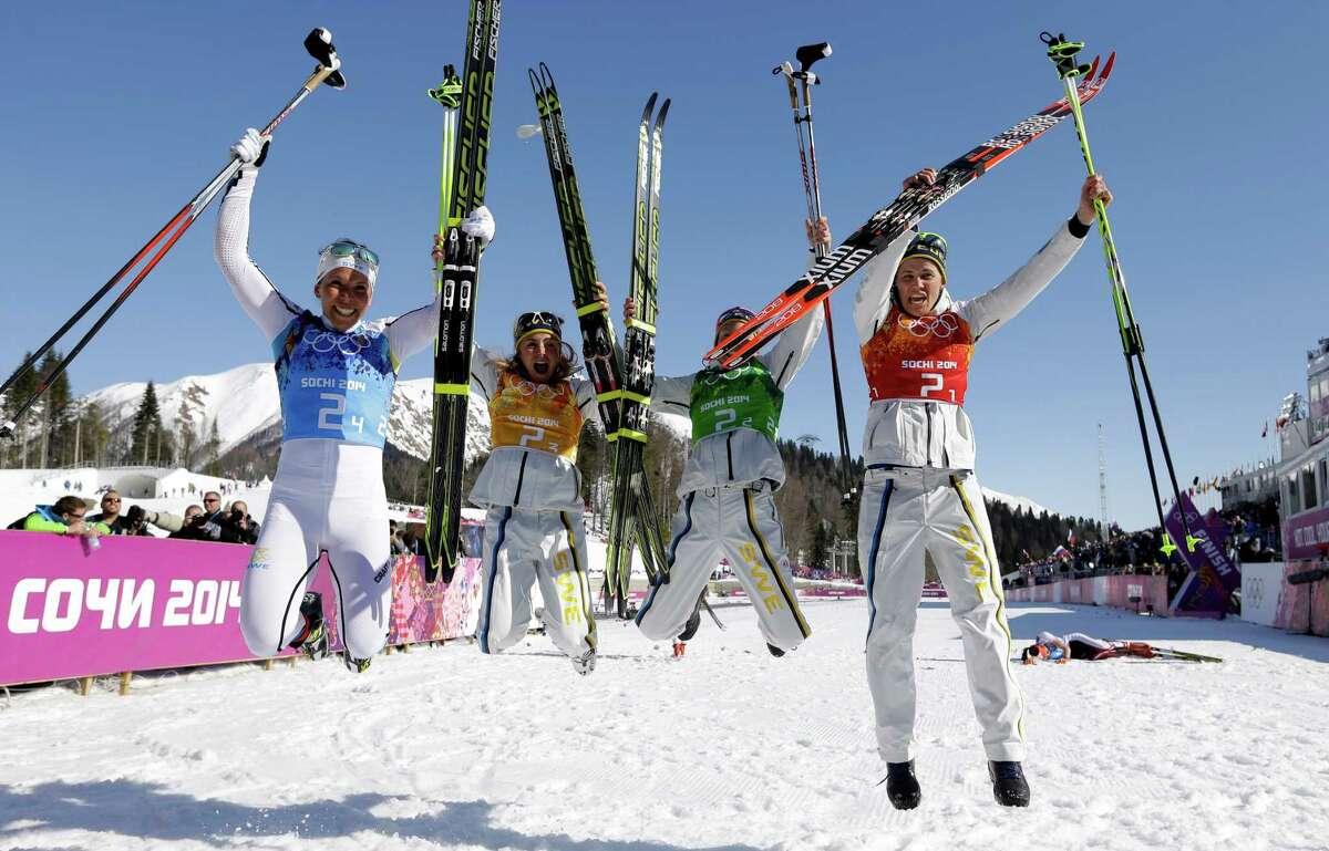 Sweden's women's 4x5K cross-country relay team Ida Ingemarsdotter, Emma Wiken, Anna Haag and Charlotte Kalla, from right, celebrate winning the gold after the women's 4x5K cross-country relay at the 2014 Winter Olympics, Saturday, Feb. 15, 2014, in Krasnaya Polyana, Russia.