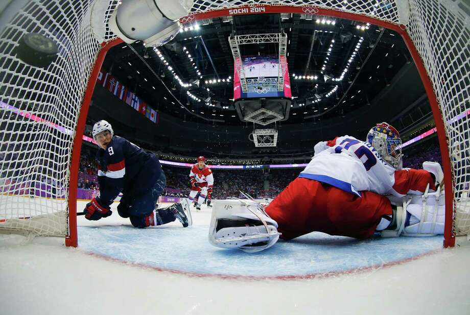 The puck hits the back of the net past Russia goaltender Sergei Bobrovski as USA forward Zach Parise looks on in the third period of a men's ice hockey game at the 2014 Winter Olympics, Saturday, Feb. 15, 2014, in Sochi, Russia. The USA won 3-2 in an overtime shootout. Photo: Julio Cortez, AP / AP2014